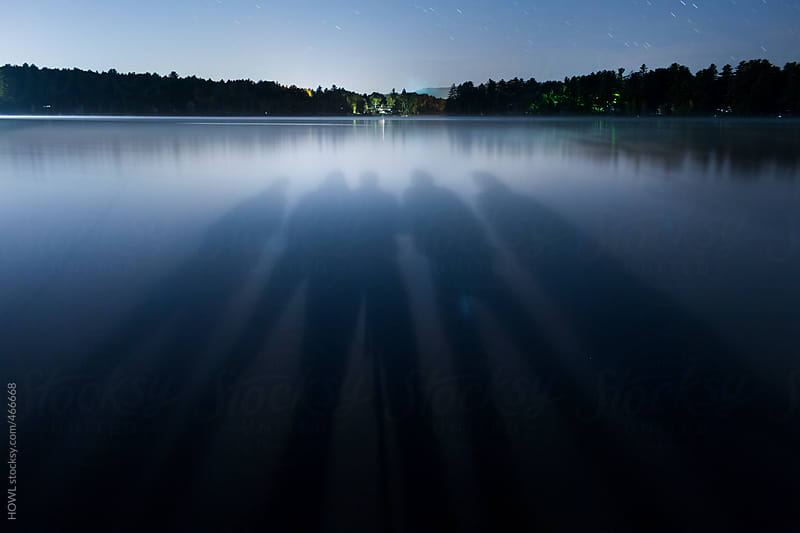The shadows of five friends on a calm lakeside evening by HOWL for Stocksy United