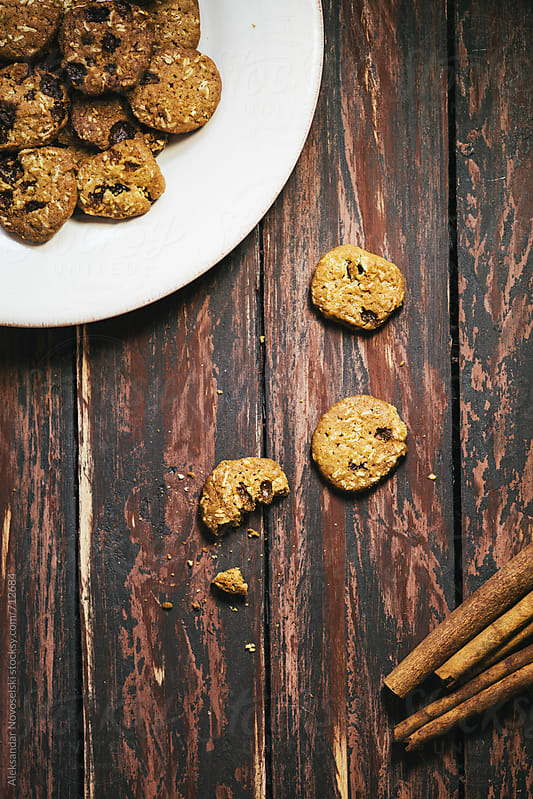 Cinnamon and biscuits on an old wooden table shot from above by Aleksandar Novoselski for Stocksy United