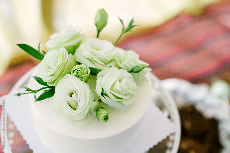 White cake with white roses by Maa Hoo for Stocksy United