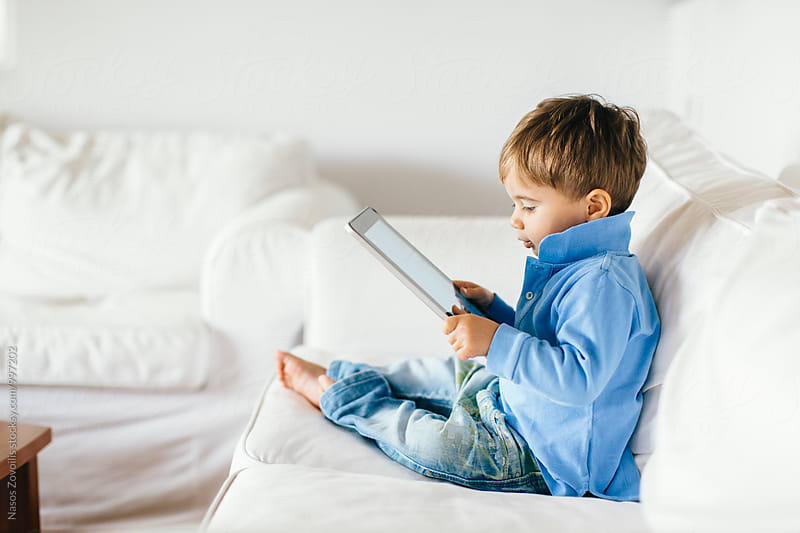 1 year old boy looking a digital tablet by Nasos Zovoilis for Stocksy United