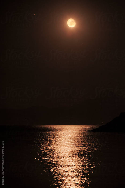 Full moon reflecting on water at night by Borislav Zhuykov for Stocksy United