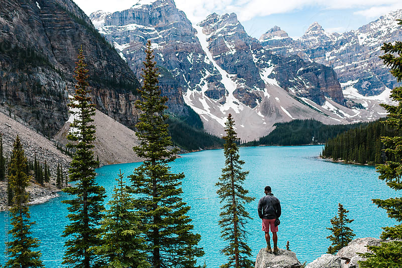 A man standing on a rock at Moraine Lake in Alberta, Canada by Kristen Curette Hines for Stocksy United