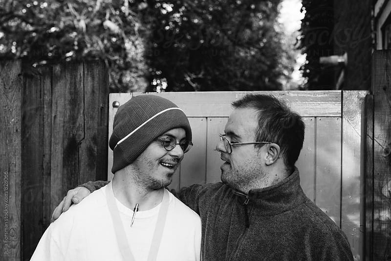 Two men with Down's Syndrome share a joke. by Julia Forsman for Stocksy United