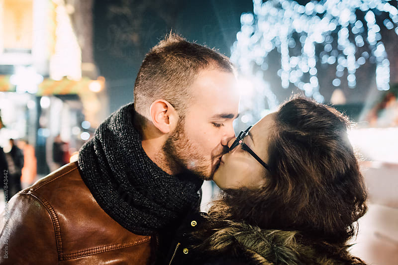 Happy couple kissing on the street by Boris Jovanovic for Stocksy United