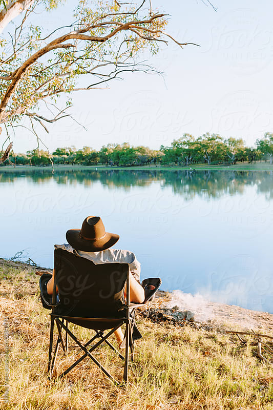 man relaxing by a river in outback Australia by Gillian Vann for Stocksy United