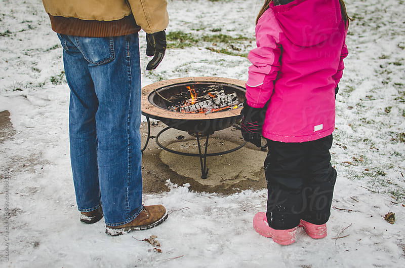 Man and child standing by a fire pit outdoors in winter by Lindsay Crandall for Stocksy United