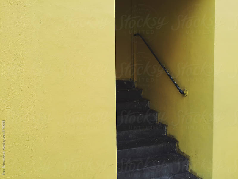 Painted yellow stairway of warehouse by Paul Edmondson for Stocksy United