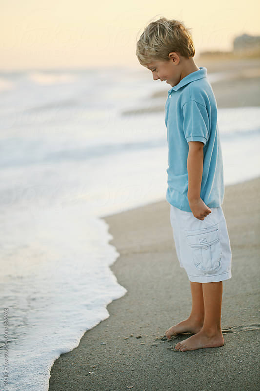 happy boy watches the ocean approach his feet by Kelly Knox for Stocksy United