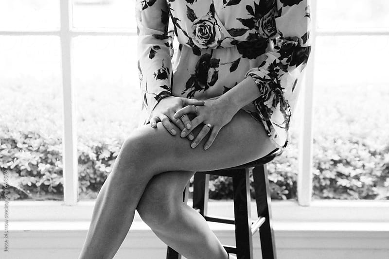 young female crossing legs while sitting on stool in front of window by Jesse Morrow for Stocksy United
