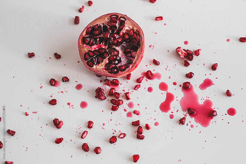 Messy pomegranate cut in half on white background by Jovo Jovanovic for Stocksy United