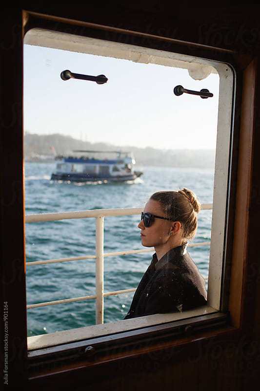 A woman gazes across the Bosphorus during her ferry journey from Asia to Europe. by Julia Forsman for Stocksy United