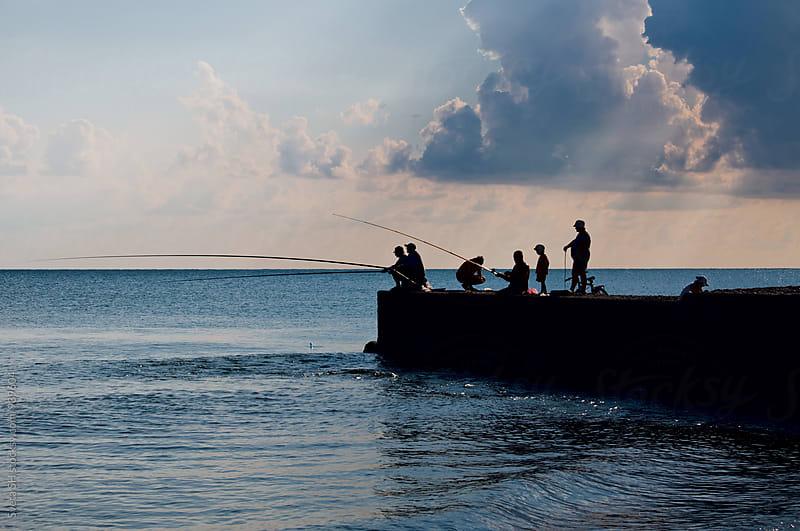 Fishermen on the pier by Svetlana Shchemeleva for Stocksy United
