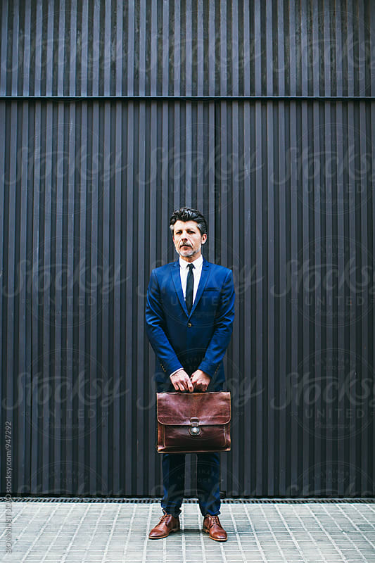 Portrait of a mature businessman holding his briefcase standing on the street. by BONNINSTUDIO for Stocksy United
