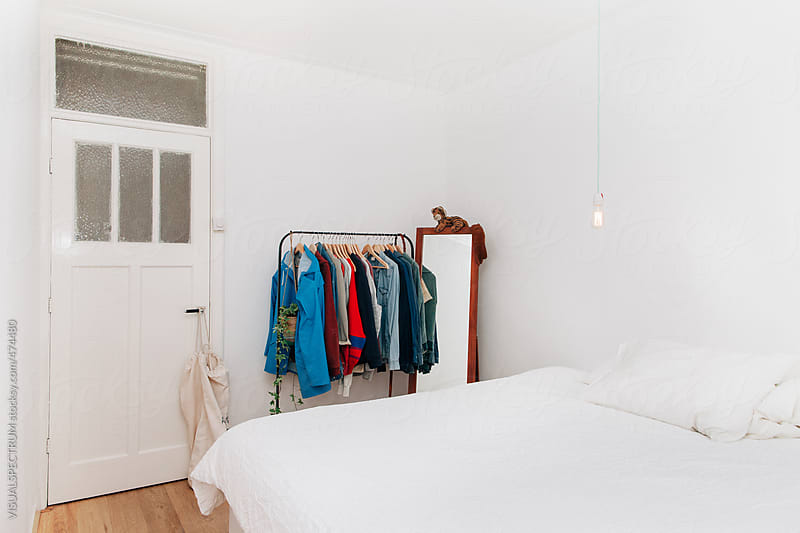 White Minimalist Bedroom With Male Clothes on Clothing Rail by VISUALSPECTRUM for Stocksy United