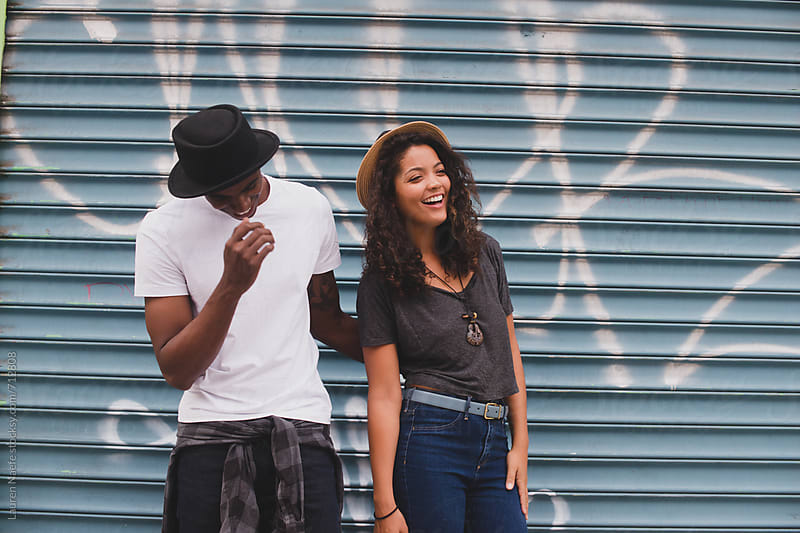 Young couple laughing, hanging out in the city by Lauren Naefe for Stocksy United