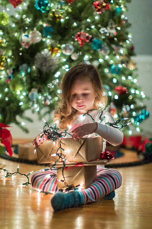 Toddler playing with christmas gifts and holiday lights by Jakob for Stocksy United