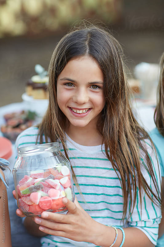 Young beautiful girl with a jar filled with candy and gummies by Miquel Llonch for Stocksy United
