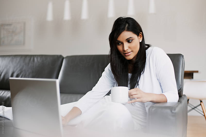 Young Woman with Laptop on Sofa by WAA for Stocksy United