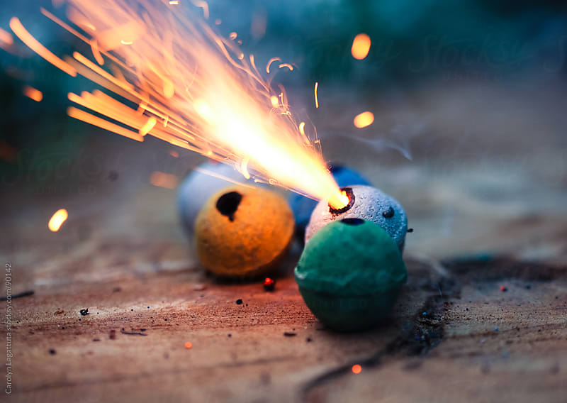 Colorful clay smoke bombs with sparks flying by Carolyn Lagattuta for Stocksy United