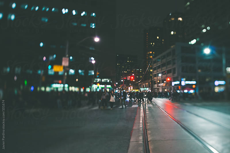 group of people walking around the city at night by Javier Pardina for Stocksy United