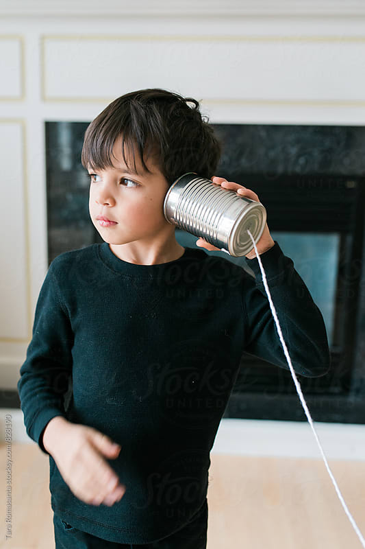 child listens on a tin can telephone by Tara Romasanta for Stocksy United