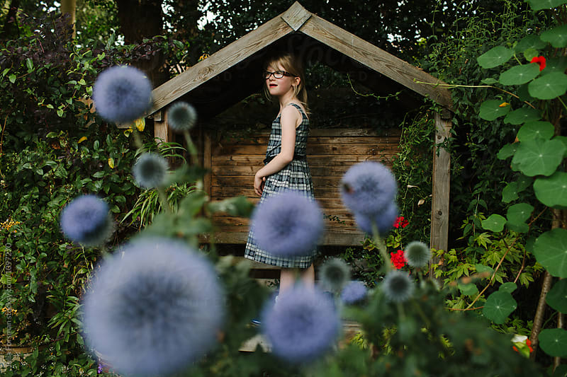 A young girl stands on a wooden bench in a garden filled with flowers. by Julia Forsman for Stocksy United