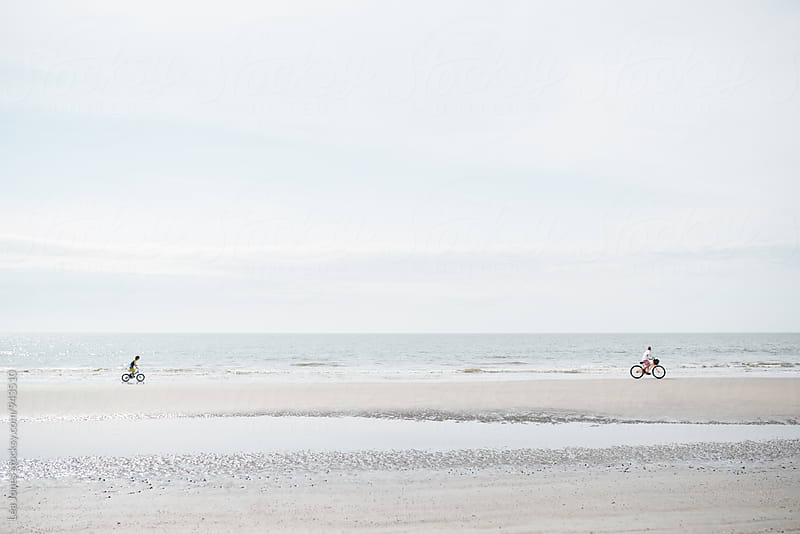 kids riding their bikes by the sea by Léa Jones for Stocksy United