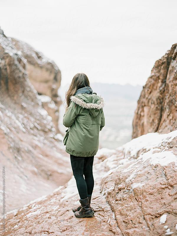 Woman on snowy rocks by Daniel Kim Photography for Stocksy United