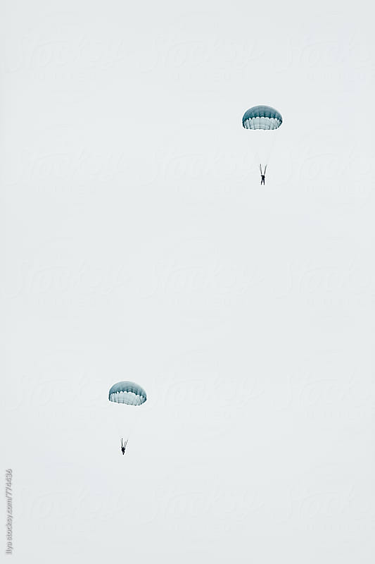 Two parachutists (skydivers) flying in the sky by Ilya for Stocksy United