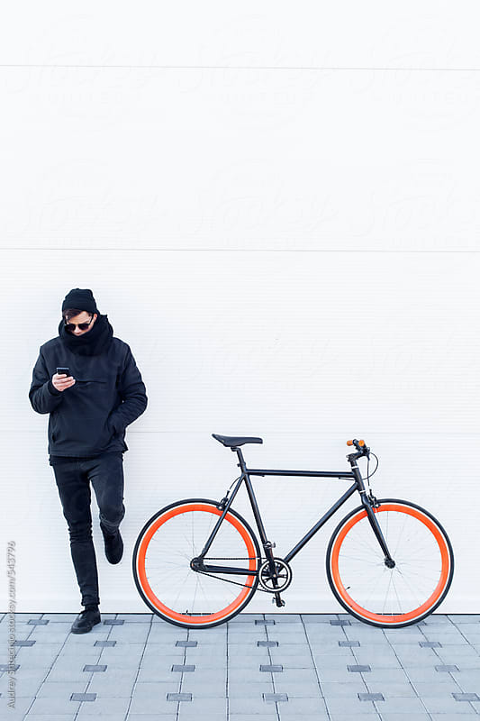 Cool young man in black outfit typing message on cellphone next to his bike. by Audrey Shtecinjo for Stocksy United