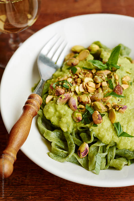 Spinach pasta with avocado pesto and pistachios by Harald Walker for Stocksy United