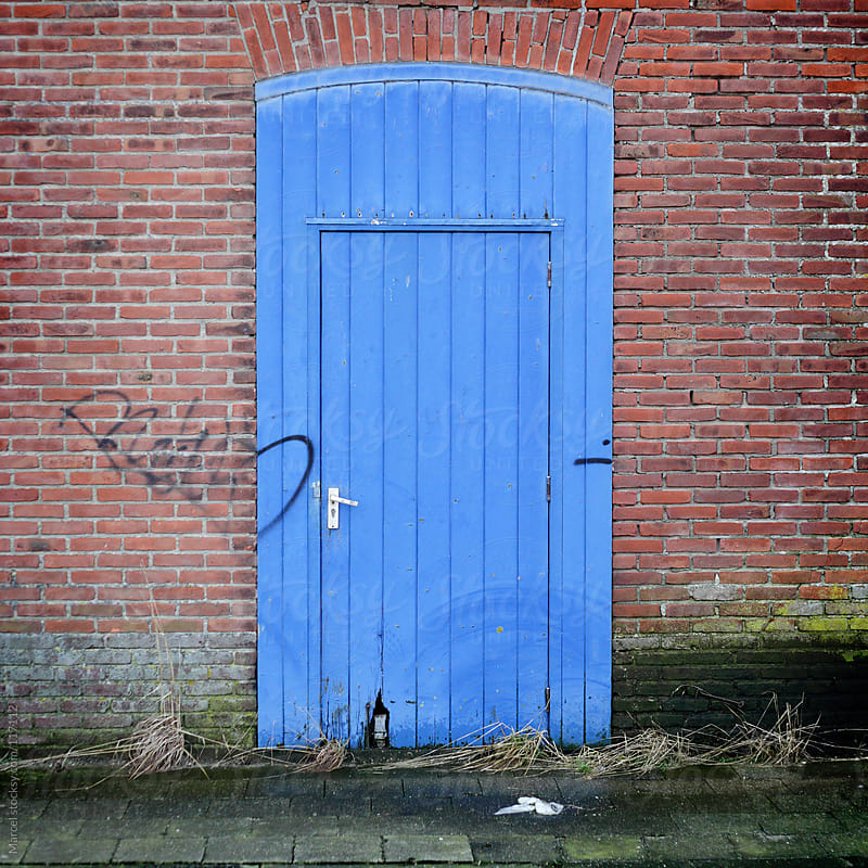 The blue door of an old building with brick wall by Marcel for Stocksy United
