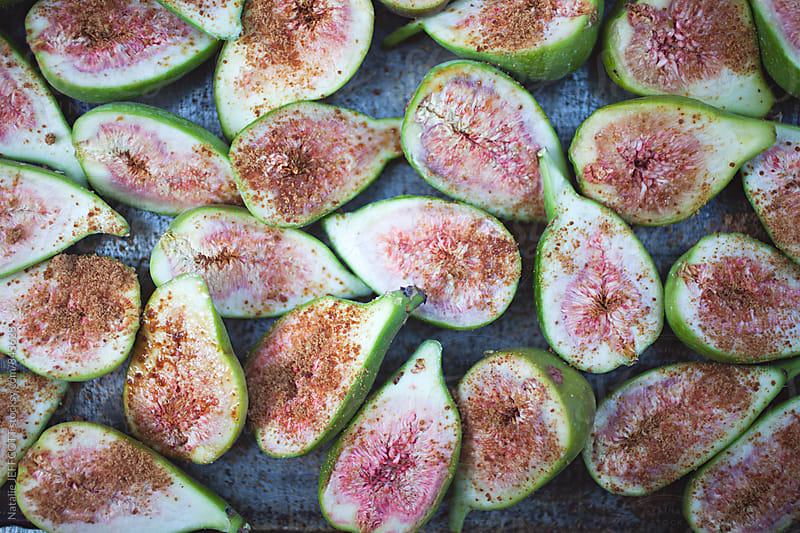 Homegrown organic figs cut in half on tray sprinkled with sugar ready to bake by Natalie JEFFCOTT for Stocksy United