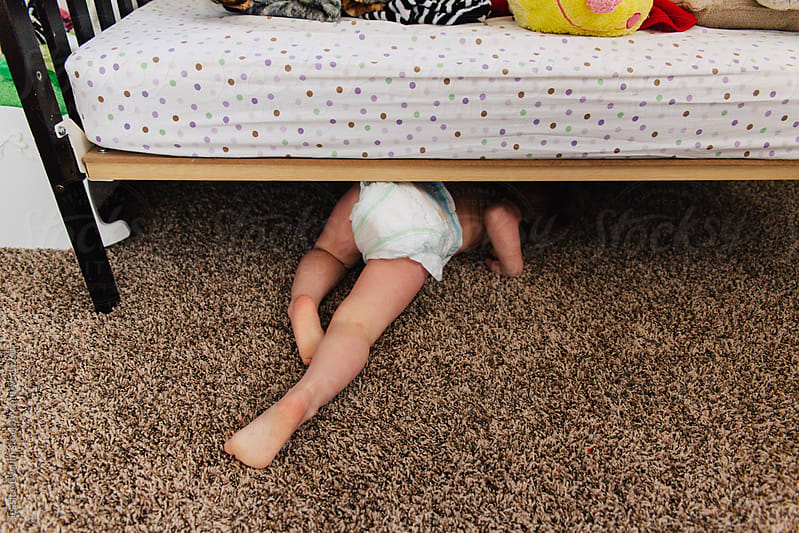 Small child crawling under bed by Jessica Byrum for Stocksy United