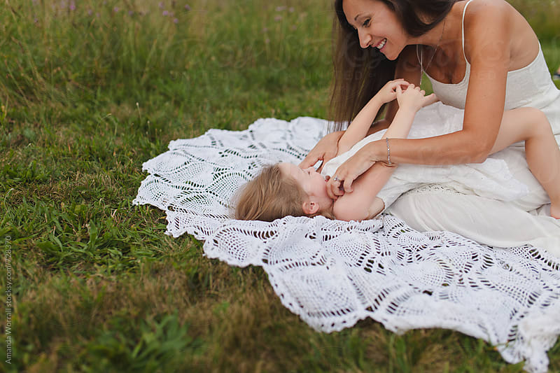 Mother tickling her daughter on a blanket in the grass by Amanda Worrall for Stocksy United