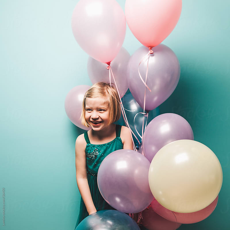 Girl Holding Balloons by Lumina for Stocksy United