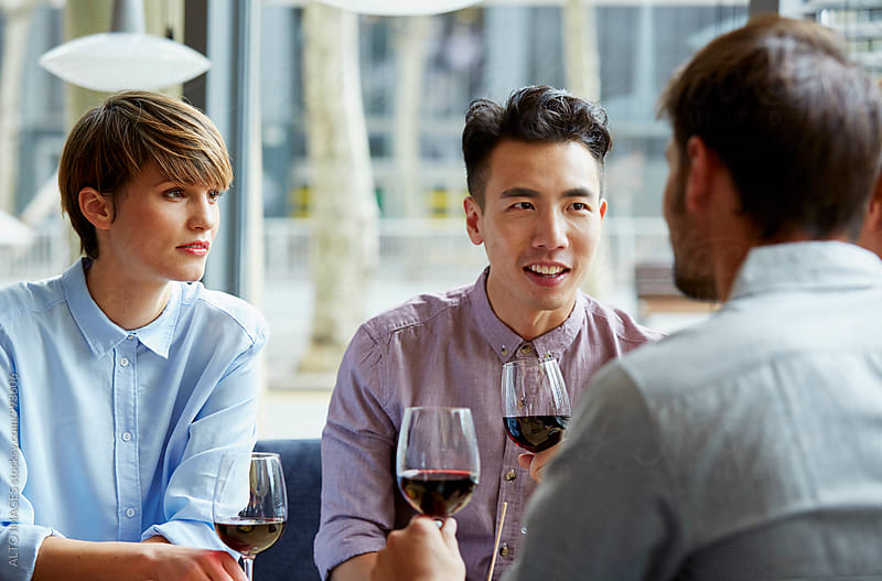 Friends Having Wine While Talking In Restaurant by ALTO IMAGES for Stocksy United