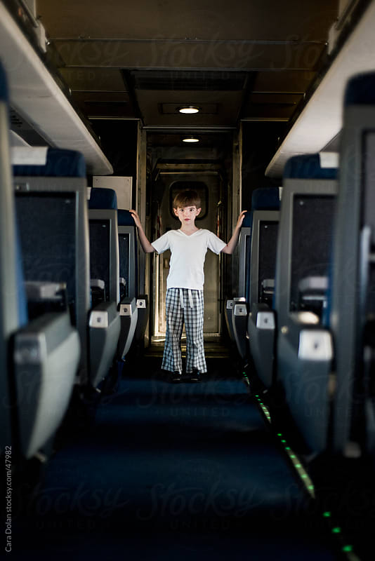 Boy stands alone on an empty train by Cara Dolan for Stocksy United