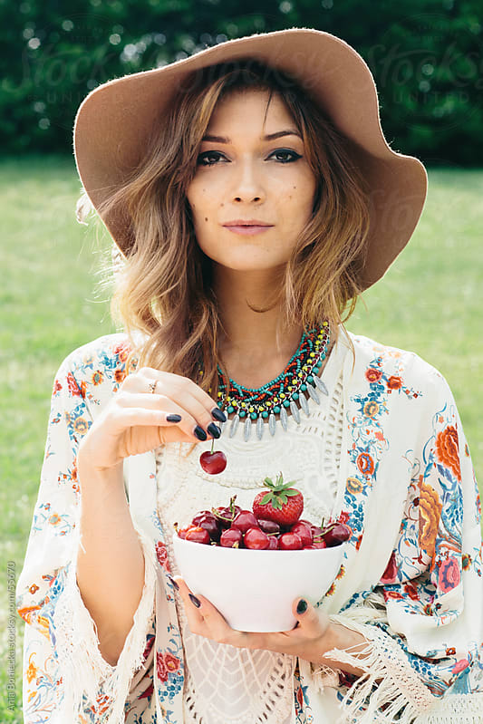 Stylish woman in a hat with a bowl of cherries by Ania Boniecka for Stocksy United