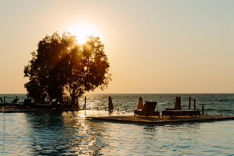 Sunset over the pool and sea by Paul Phillips for Stocksy United