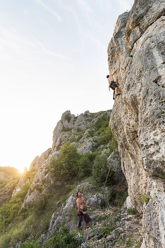 Two rock climbers climbing outdoor on a natural rock wall by Jovana Milanko for Stocksy United