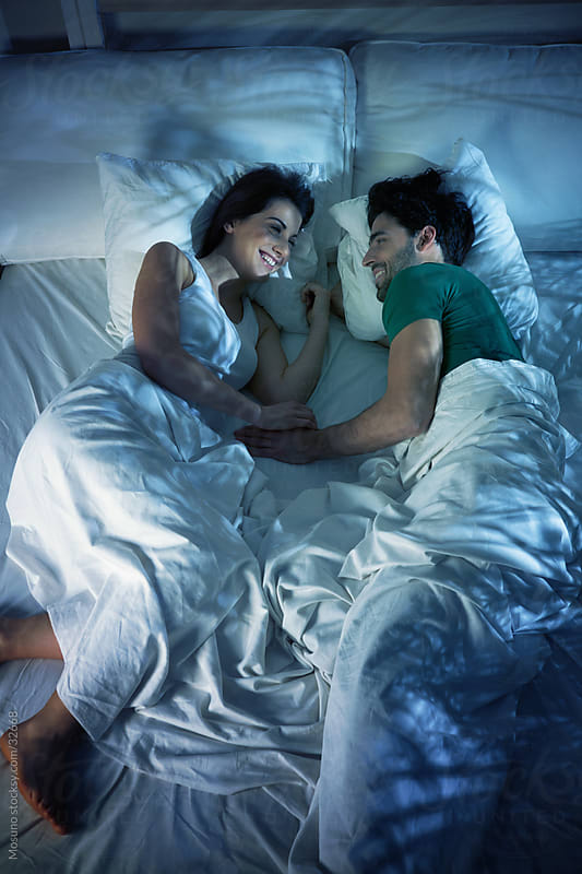Young couple talking and laughing in bed before the sleep. by Mosuno for Stocksy United