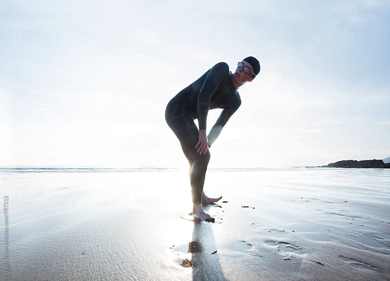Triathlete on beach. by Hugh Sitton for Stocksy United