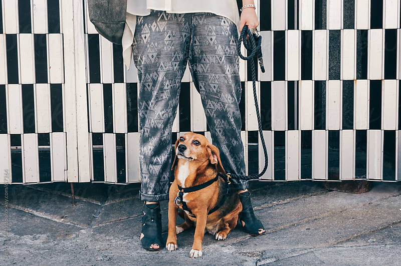 Woman and her dog standing in front of a grate by Deirdre Malfatto for Stocksy United