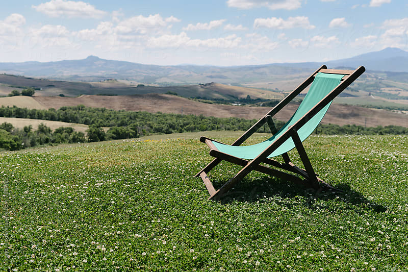 Deckchair on hill in Tuscany by Kirstin Mckee for Stocksy United