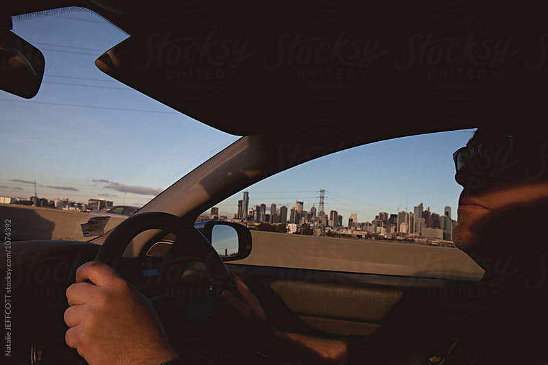 A man in Melbourne, Australia driving in car at sunset with city in background by Natalie JEFFCOTT for Stocksy United