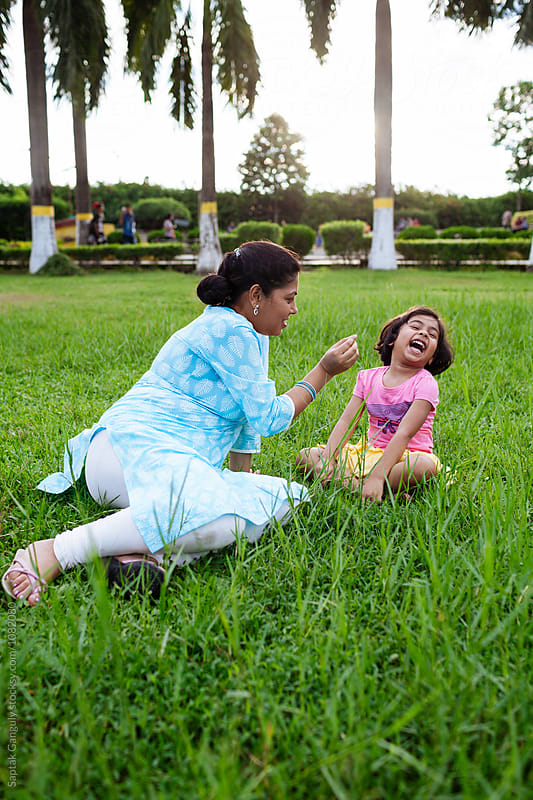 Mother and daughter sharing cheerful moment outdoors by Saptak Ganguly for Stocksy United