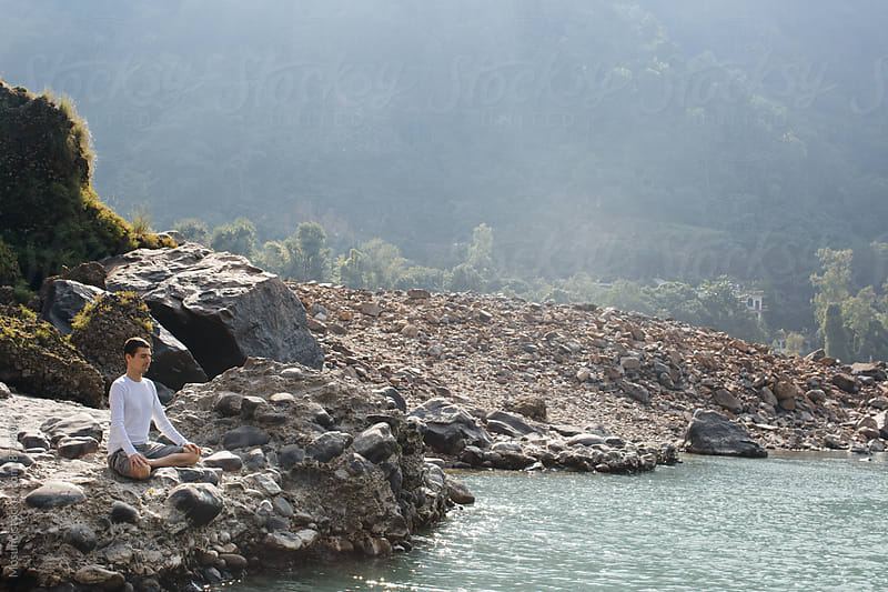 Young Man Meditating by the Holy Ganges by Mosuno for Stocksy United