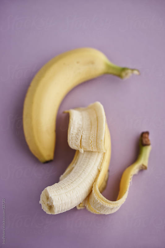 Food: Two bananas on purple background, pastel colours by Ina Peters for Stocksy United