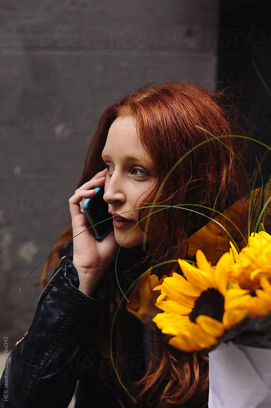 Young Woman Calling on the Phone Holding Sunflowers  by HEX . for Stocksy United